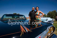 Happy proud hispanic couple standing near their customized classic impala show car in Northern California.